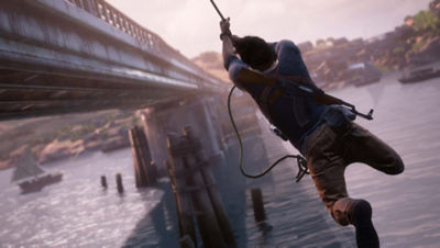 PS4 Uncharted 4 A Thief's End screenshot featuring Nathan Drake swinging on a rope, next to a bridge over the water.